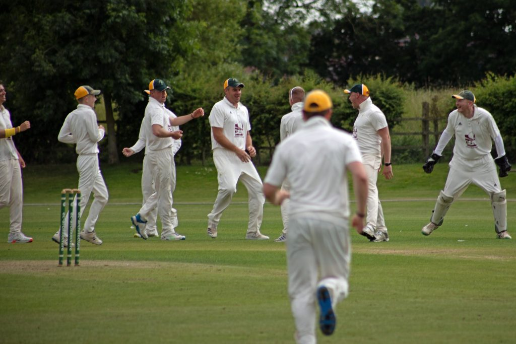 The CACC First XI celebrate taking a wicket
